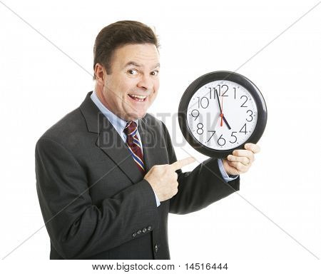 Businessman eagerly pointing to a clock that reads almost 5:00 pm.  He's ready to go home.  Isolated.