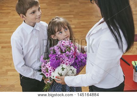 Boy And Girl Children Give Flowers As A School Teacher
