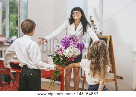 Boy And Girl Give Flowers As A School Teacher In Teacher's Day