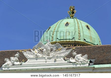 The cupola of Hofburg Palace against blue sky at summer midday