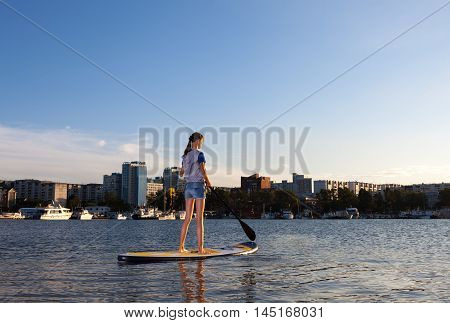 Young woman on Stand Up Paddle Board. SUP. Shape of a city on background