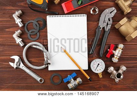 Notebook and plumber tools on wooden background