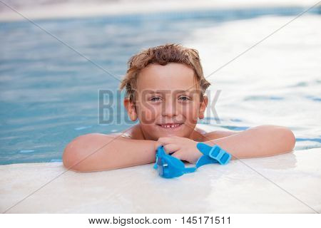 Funny blond boy cooling off in the pool