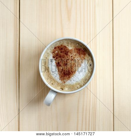 frothy coffee with cinnamon sprinkled in heart shape bright wooden background top view / favorite coffee with milk and cinnamon