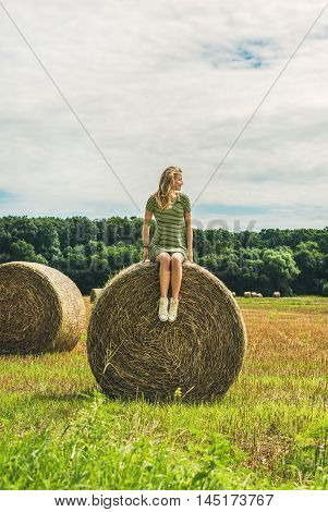 Young blond lady sitting on haystack and looking away on sunny summer day, Badasconytomaj, Hungary