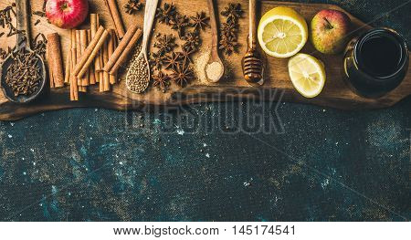 Ingredients for making mulled wine. Wine in glass bottle, honey, lemon, apples and spices on wooden board over old blue painted plywood background. Top view, copy space, horizontal composition