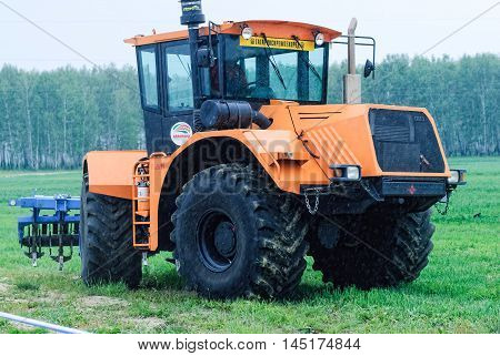 Tyumen, Russia - June 24, 2016: The 5th open championship of Russia on a plowed land. Operator plows the site on Belarus tractor in rainy weather