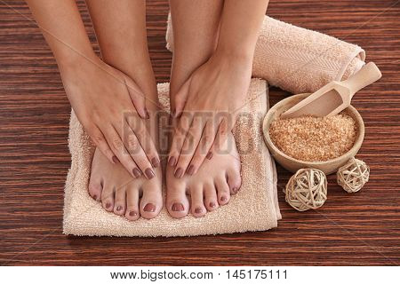 Female hands and feet with brown pedicure on towel