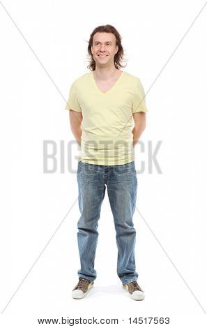Full length portrait of adult man over 30 years with hair to shoulders in a shirt, jeans and sneakers with a little paunch, which has removed hands behind back, looking up and smiling