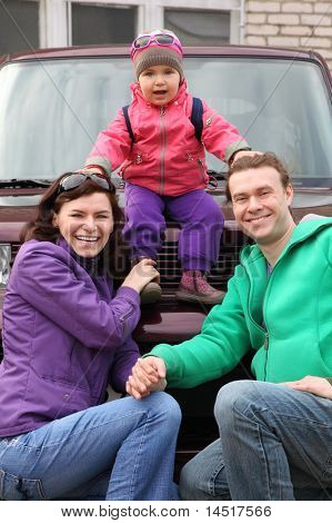 Happy family in outwear - mother and father hunker down in front of car and support little daughter sitting on car