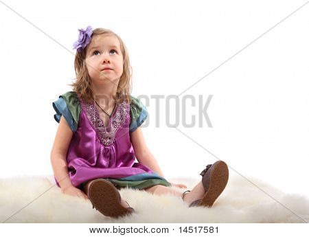 Little blond girl sitting on a fluffy carpet and thoughtfully looks up