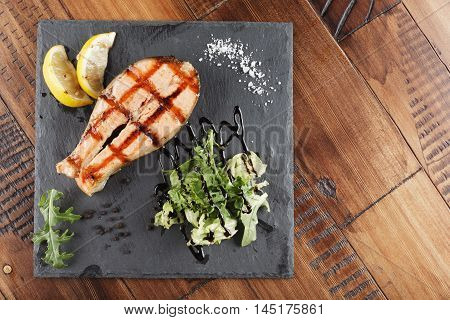 Salmon fish steak with lemon and greens on a shale surface. wooden background
