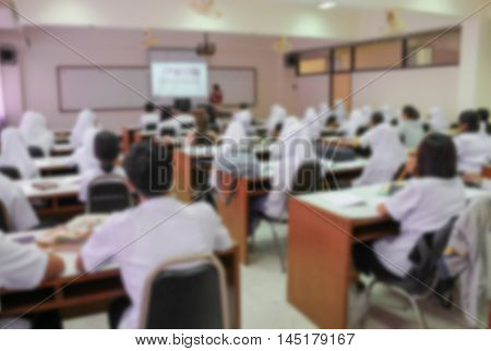 blurred focus students sitting in a lecture room with the teacher in front of the class with white projector slide screen  view from back of the classroom