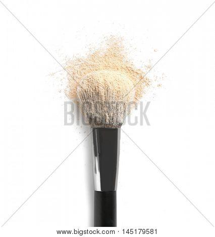 Make up brush and beige eye shadows on white background