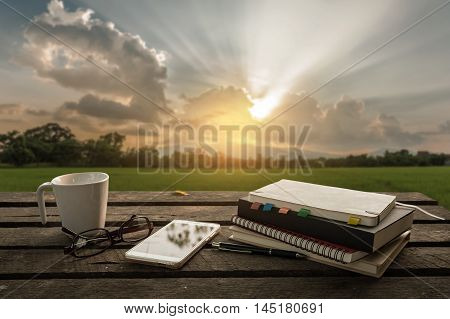 Smartphone notebooks coffee cup glasses and pen put down on outdoor wood table in morning time on weekend. Freelance business working concept