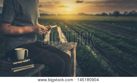 Young woman using her smartphone seriously while sitting outdoor in morning time on weekend with nature view in blurry background. Freelance business working and phone addiction concept with vintage filter effect