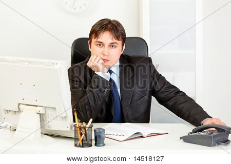 Thoughtful elegant business man sitting at desk in office
