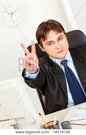Smiling elegant business man sitting at office desk and showing victory gesture