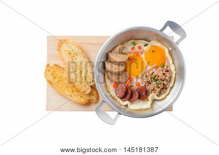 Top view of Vietnamese style pan-freid egg with Chinese sausage minced pork Vietnamese sausage in metal pan on wood plate with toast isolated on white background