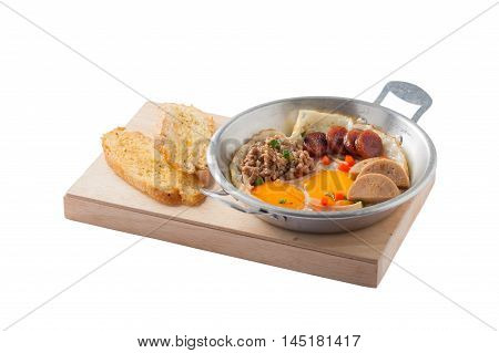 Vietnamese style pan-freid egg with Chinese sausage minced pork Vietnamese sausage in metal pan on wood plate with toast