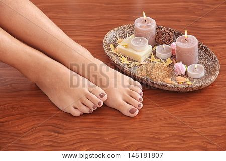 Female feet with brown pedicure and spa composition on wooden background