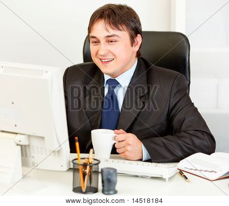 Laughing business man with cup of coffee looking at computer monitor