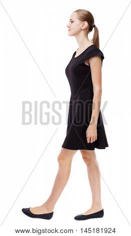 back view of walking woman. beautiful girl in motion. Isolated over white background. Blonde in a short black dress goes on the side