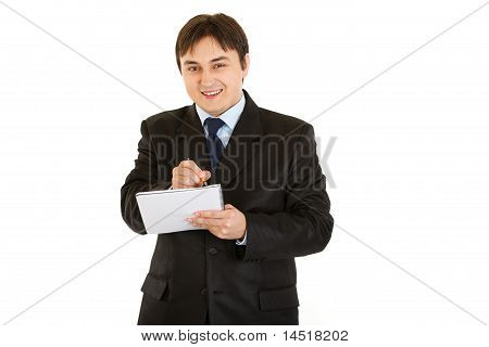 Smiling modern businessman making notes in notebook isolated on white