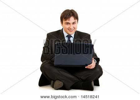 Smiling businessman sitting on floor and working on laptop isolated on white