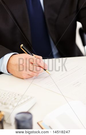 Business man sitting at office desk and signing protocol. Close-up.