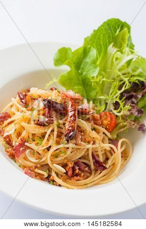 Thai Japanese and European fusion food style spicy pasta with bacon and dried chili in ceramic dish