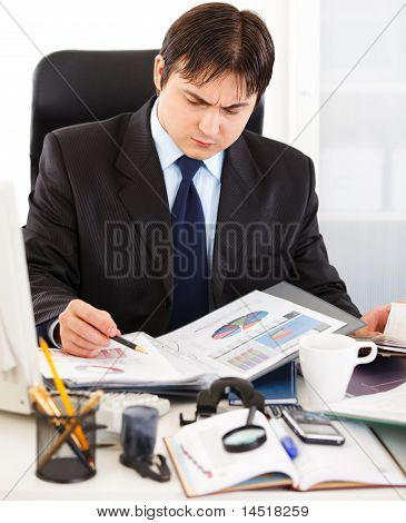 Thoughtful business man sitting at office desk and working with financial documents
