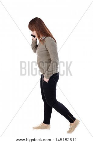 side view of a woman walking with a mobile phone. back view of girl in motion. with his hand in the pocket of a girl talking on the phone and go to the right.