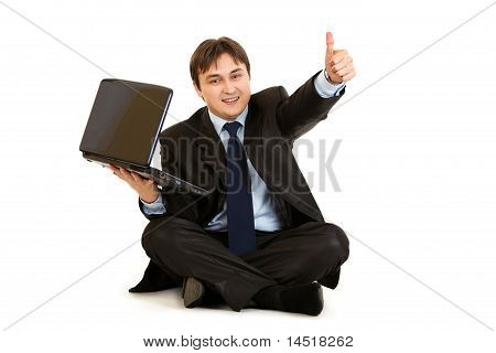 Smiling businessman sitting on floor with laptop showing thumbs up gesture isolated on white