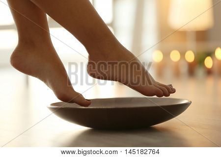 Female feet in spa wooden bowl on blurred background