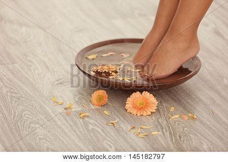 Female feet in spa bowl on wooden background