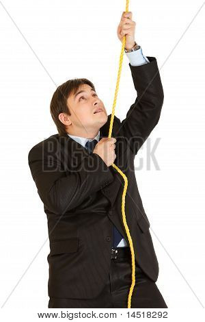 Stubborn young businessman climbing up on rope isolated on white