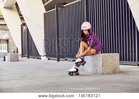Smiling girl sitting on the stairs and puts on roller skates. Happy women getting ready for skating outdoors. Sport lifestyle.