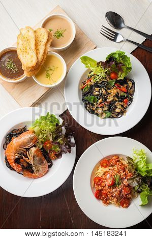 Top view of modern cuisine set including Pasta dried chili Black pasta with clams Carbonara pasta with bacon and Onion-Corn-Mushroom soup with toast on wood table in restaurant