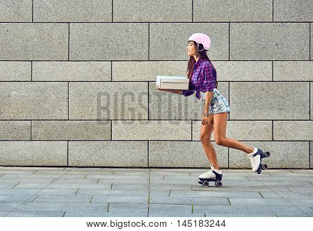 Delivery on roller skates by beautiful girl in helmet. Beautiful girl rollerblading Beautiful girl rollerblading. Young woman on roller skates with box or pizza in hands.