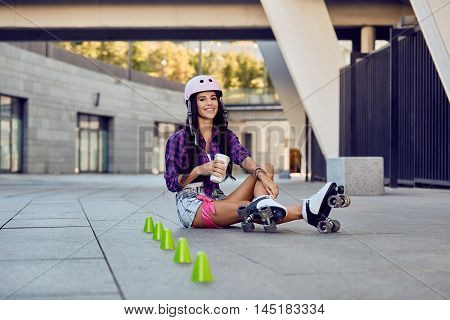 Young woman take a rest after riding roller skates and drinking coffee or tea sitting on the pavement on street. Happy girl enjoying roller skating rollerblading in urban park.