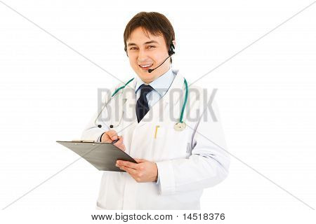 Smiling medical doctor with headset holding clipboard in hand isolated on white