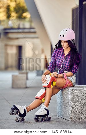 Active lifestyle girl is going to ride on roller skates. Beautiful girl puts protection equipment for rollerblading. Attractive teenager sitting on street a sunny day.
