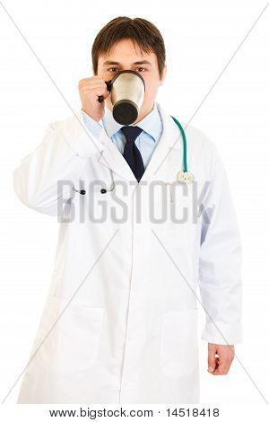 Medical doctor in uniform drinking coffee isolated on white