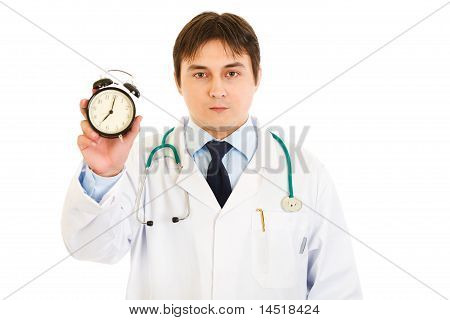Serious medical doctor holding alarm clock in hand isolated on white