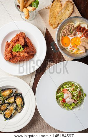 Top view of modern cuisine set including spring rolls pan fried egg Korean style deep fried chicken baked mussels and sunflower sprout salad on wood table in restaurant