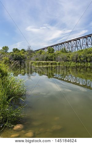 A long and tall railroad bridge reflecting in a river.