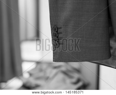 Buttons on sleeve of business suit unfocused dressing room on the background