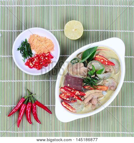Green chicken curry in coconut milk served with side dish as minced dried shrimp,sliced red chili,sliced kaffir lime leaves and green lemon on bamboo.