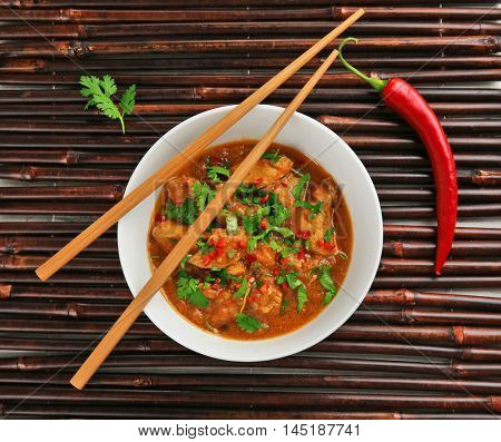 Tasty chicken curry in plate and spices on bamboo background